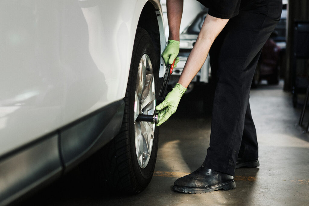 mechanic removing bolts from tire