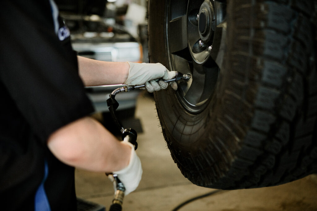 mechanic filling a tire with air